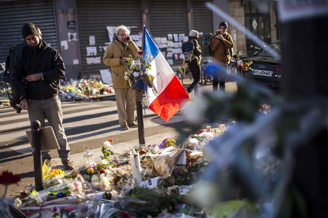 Dix jours après le drame, des passants se... (PHOTO LIONEL BONAVENTURE, AFP)