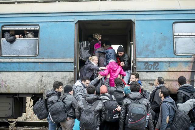 Des réfugiés et migrants montent à bord d'un... (PHOTO ROBERT ATANASOVSKI, AFP)