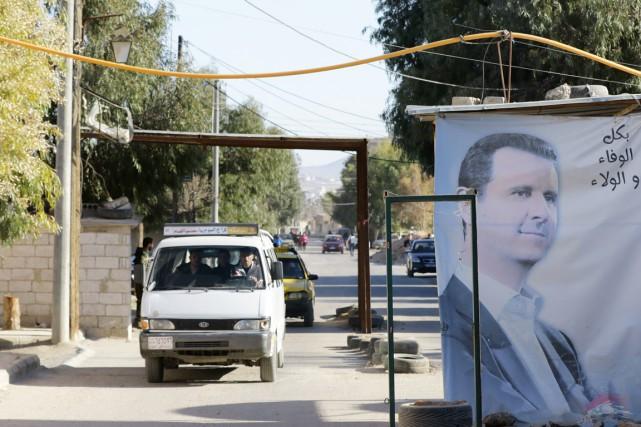 Des véhicules circulent près d'une affiche à l'effigie... (PHOTO LOUAI BESHARA, ARCHIVES AFP)