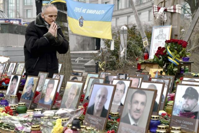 Un homme prie parmi les portraits des victimesdu... (PHOTO SERGEI SUPINSKY, AFP)