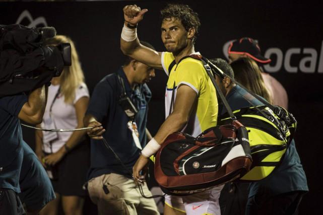 Rafael Nadal sort du terrain en saluant le... (Photo YASUYOSHI CHIBA, AFP)