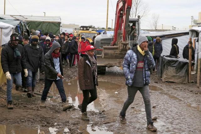 Des migrants et réfugiés marchent dans la boue... (PHOTO PASCAL ROSSIGNOL, REUTERS)