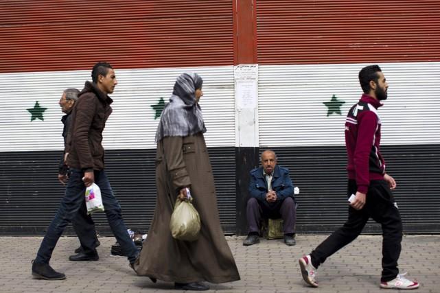 Des habitants de Damas passent devant un rideau... (PHOTO HASSAN AMMAR, AP)