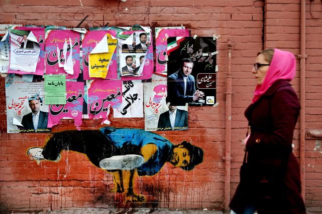 Une femme passe devant un mur où des... (PHOTO EBRAHIM NOROOZI, AP)