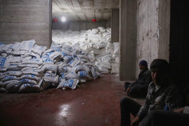 Des hommes sont assis près de sacs de... (PHOTO ABD DOUMANY, ARCHIVES AFP)