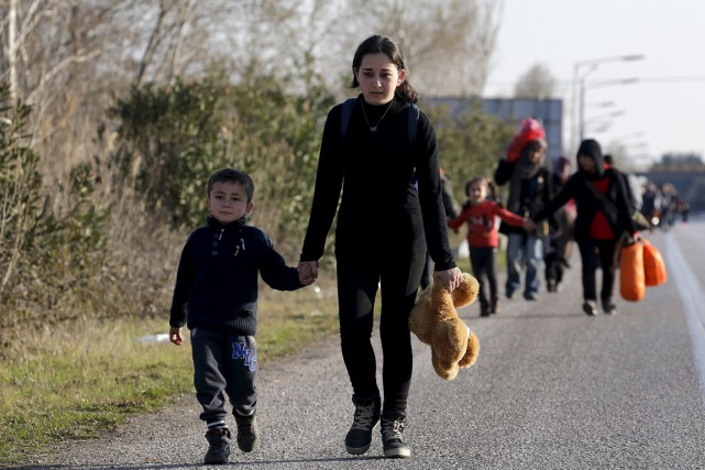 Des migrants marchent le long d'une autoroute entre... (Photo Yannis Behrakis, REUTERS)