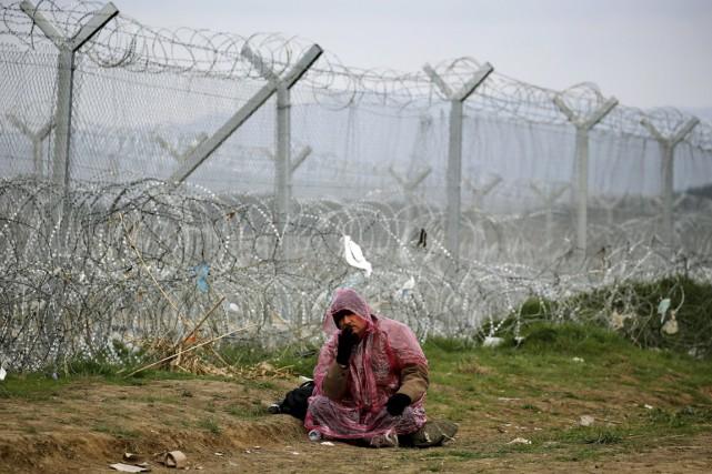 Un réfugié syrien est assis devant une clôture... (PHOTO YANNIS BEHRAKIS, REUTERS)