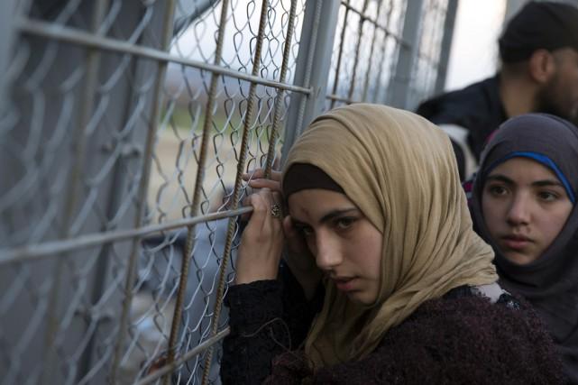Une jeune Syrienne se penche sur une clôture... (Associated Press)