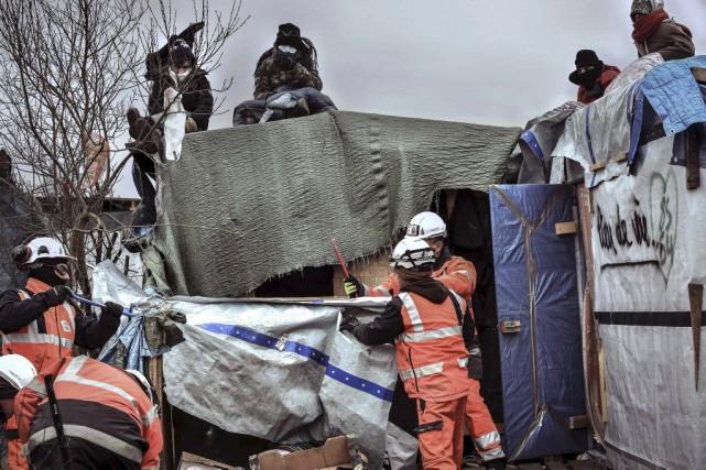 Des migrants s'assoient sur les toits des abris... (PHOTO PHILIPPE HUGUEN, AGENCE FRANCE-PRESSE)