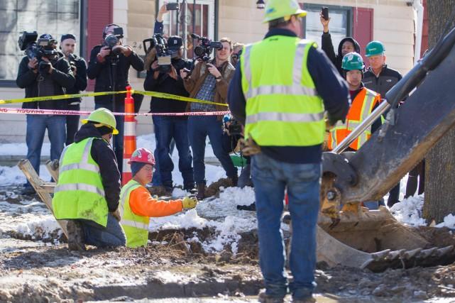 Des travailleurs remplacent une conduite à Flint, vendredi.... (Photo Geoff Robins, AFP)