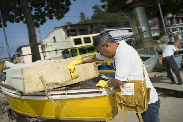 Un homme enlève de l'eau stagnante d'une barque... (AP, Leo Correa)