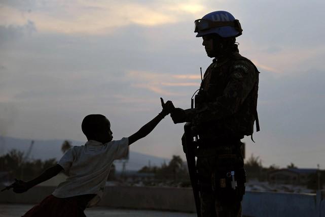 Un soldat brésilien en mission pour la Minustahs'amuse... (PHOTO VANDERLEI ALMEIDA, ARCHIVES AFP)