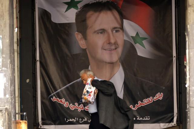 Un homme passe devant une affiche à l'effigie... (PHOTO LOUAI BESHARA, ARCHIVES AFP)