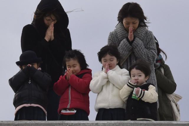 Familles de Sendai,lors des commémorations du tsunami, vendredi.Il... (AFP, Toru Yamanaka)