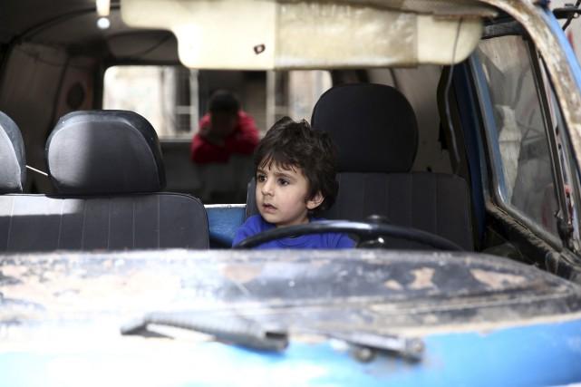 Une jeune Syrien joue dans une voiture au... (Agence France-Presse, Abd Doumany)