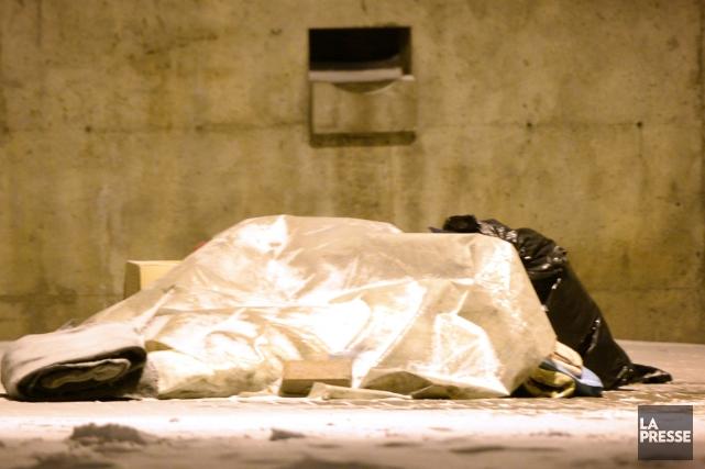 Un itinérant dort sous un abri de fortune.... (La Presse)