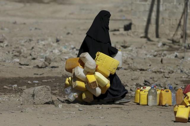 Une femme transporte des récipients pour les remplir... (PHOTO KHALED ABDULLAH, ARCHIVES REUTERS)