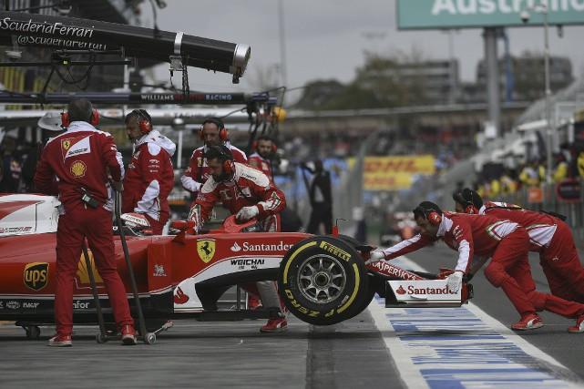 Les membres de l'écurie Ferrari poussent la voiture... (AFP, Saeed Khan)