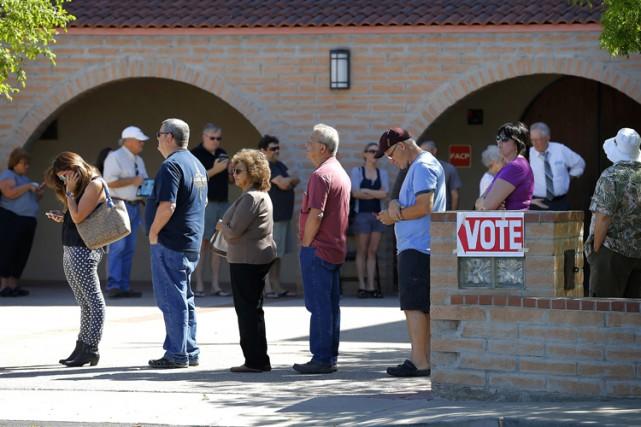 Des gens font la file devant un bureau... (PHOTO AP)