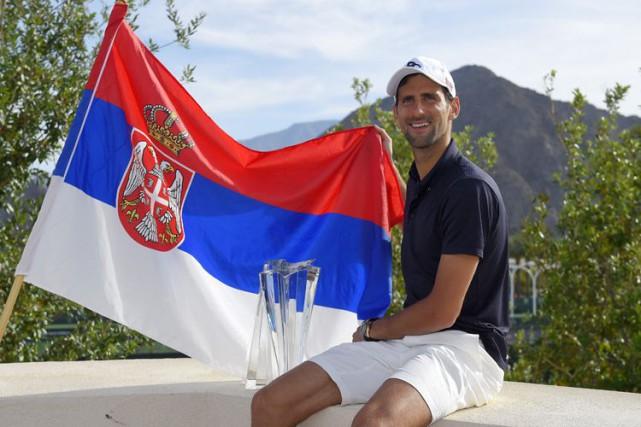 Novak Djokovic pose avec le drapeau serbe et... (AP)