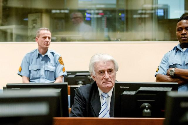Radovan Karadzic, en costume foncé et cravate rayée... (Photo Robin van Lonkhuijsen, AFP)