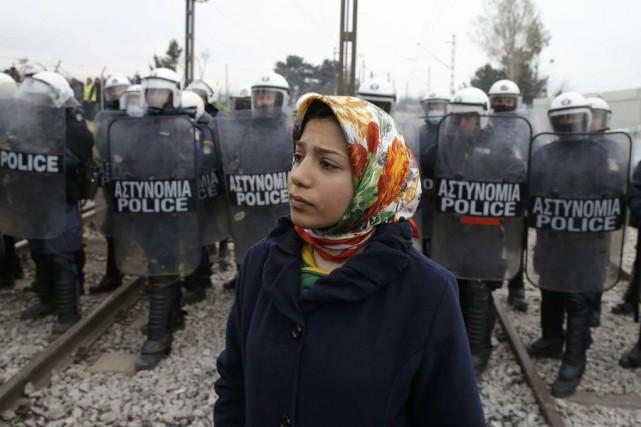 Une migrante devant des policiers à la frontière... (PHOTO MARKO DJURICA, REUTERS)