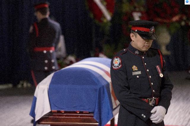 Un garde surveille le cercueil de Rob Ford.... (La Presse Canadienne)