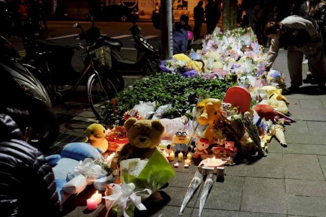 Des gens déposent fleurs et animaux en peluche... (PHOTO TYRONE SIU, REUTERS)