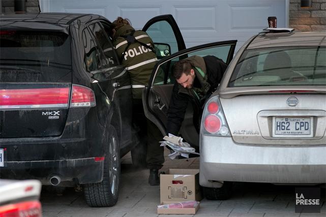 Des policiers fouillent des voitures, à Sainte-Marthe-sur-le-Lac, dans... (Photo David Boily, La Presse)