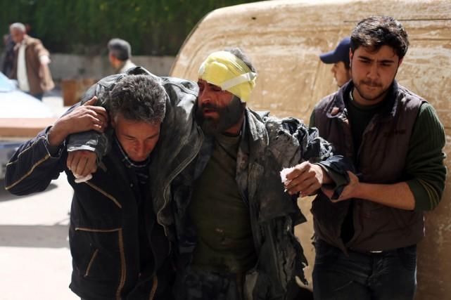 Des hommes aident un blessé, après des frappes... (Photo AMER ALMOHIBANY, AFP)