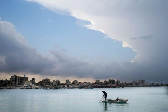 Un pêcheur palestinien jette son filet dans la... (Mohammed Abed, Archives AFP)
