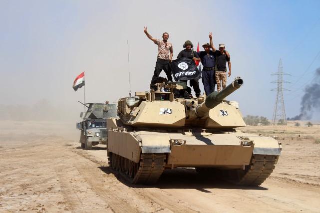 Des membres des forces armées irakiennes célèbrent sur... (PHOTO MOADH AL-DULAIMI, AGENCE FRANCE-PRESSE)