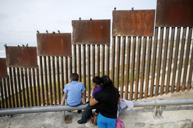 Une famille regarde en direction de barreaux métalliques... (PHOTO GREGORY BULL, ARCHIVES AP)
