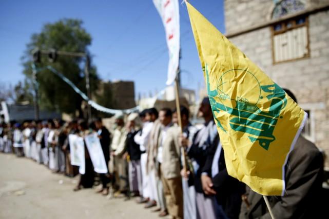 Un manifestant tient un drapeau du Hezbollah lors... (PHOTO AP)