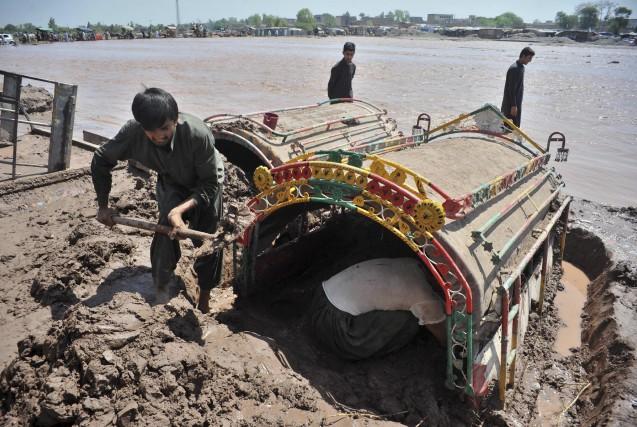 Des Pakistanais tentent de libérer un camion immobilisé... (AFP, A Majeed)