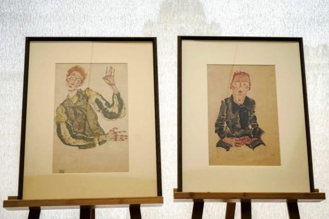 Autoportrait aux coudières et Garçon assis avec les... (PHOTO AFP)