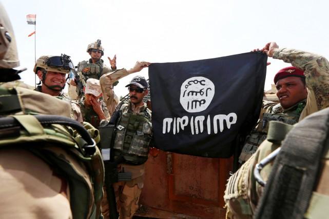 Des soldats irakiens exhibent le drapeau noir du... (PHOTO SAFIN HAMED, AFP)