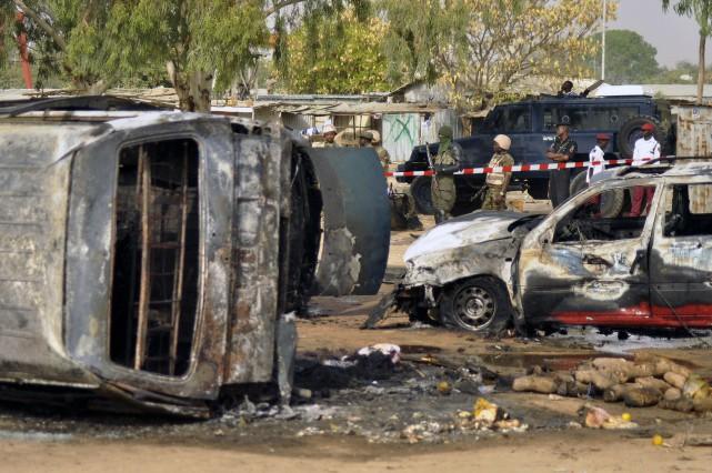 Des policiers surveillent les lieux où s'est déroulé... (AP, Sani Maikatanga)