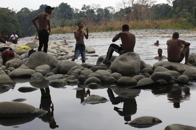 Des migrants cubains se lavent dans une rivière... (PHOTO REUTERS)