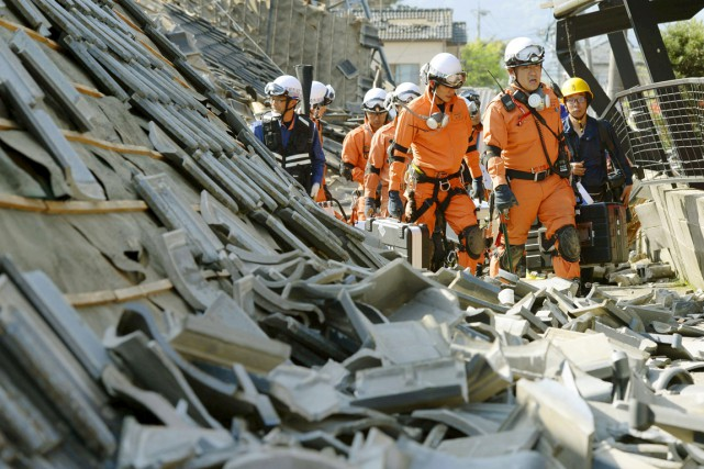 Des pompiers marchent à travers les ruines de... (PHOTO KYODO/REUTERS)