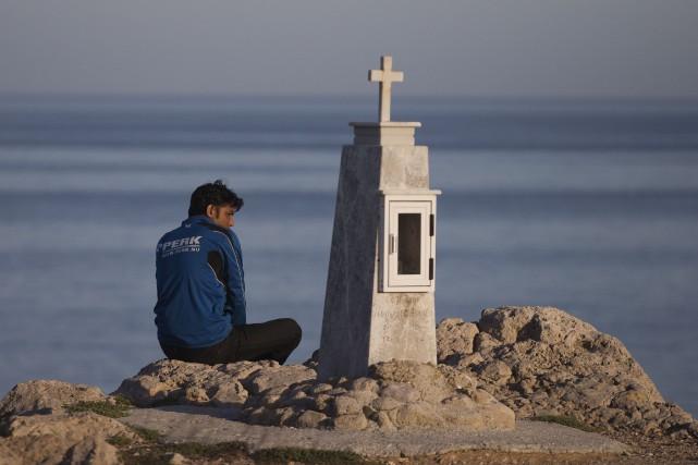 Un migrant pakistanais attend au bord de la... (AP, Petros Giannakouris)