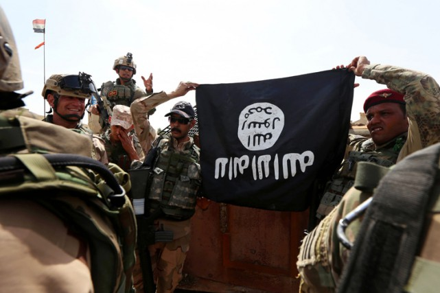 Des soldats irakiens ont saisi un drapeau de... (PHOTO AFP)