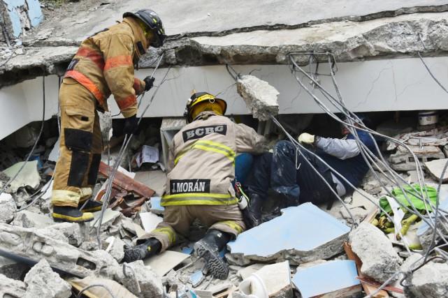 Des pompiers-secouristes fouillent les décombres d'un immeuble en... (PHOTO LUIS ACOSTA, AFP)