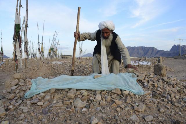 Malik Abdul Hakim travaille auprès d'une tombe d'un... (AFP, Jawed Tanveer)