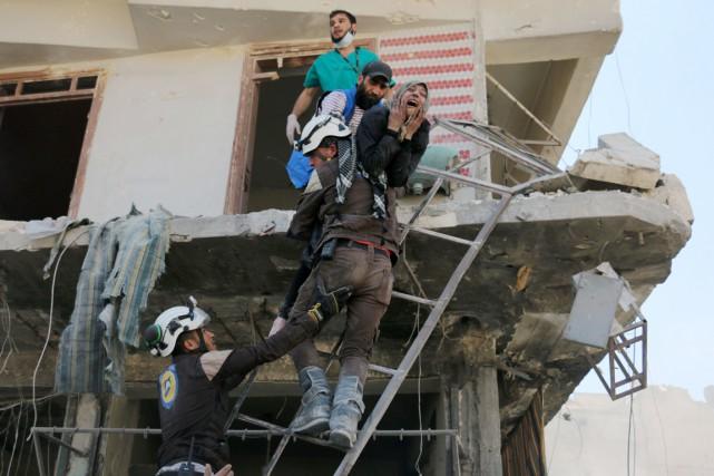 Des secouristes évacuent des résidants d'un immeuble touché... (PHOTO AMEER ALHALBI, AFP)