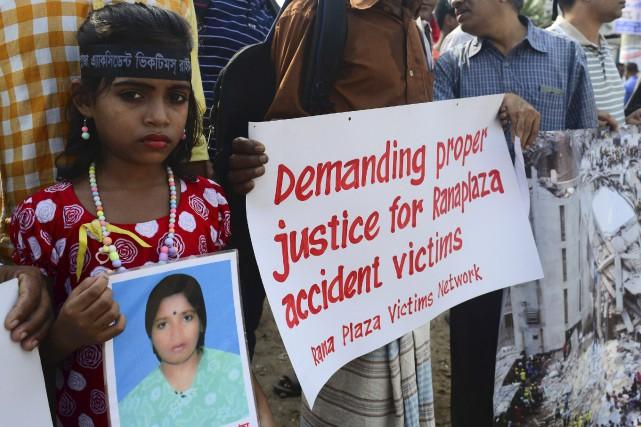 Une jeune Bangladaise tient une photo de sa... (AFP, Munir Uz Zaman)