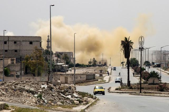 Une colonne de fumée s'élève d'une rue d'Alep... (PHOTO KARAM AL-MASRI, ARCHIVES AFP)
