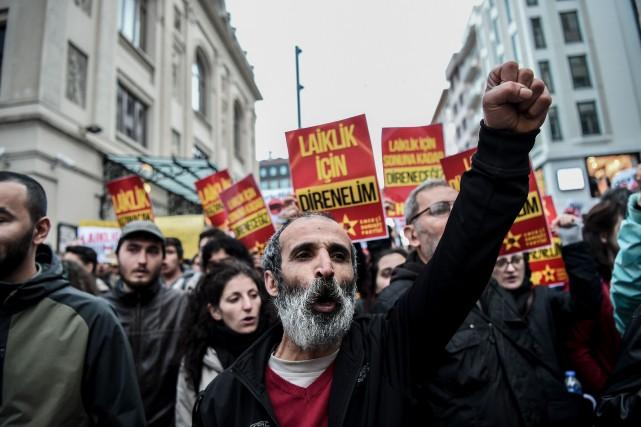 Des manifestants arborent des affiches sur lesquelles on... (PHOTO OZAN KOSE, AGENCE FRANCE-PRESSE)