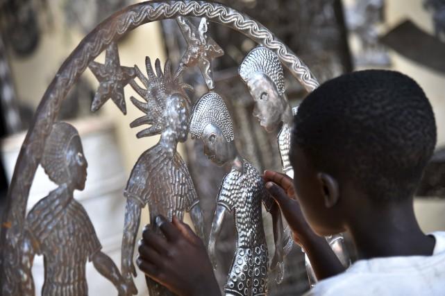 Samuel polit une oeuvre de métal dans le... (Agence France-Presse, Hector Retamal)