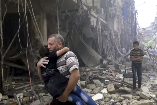 Un homme transporte un enfant après un bombardement... (AP)